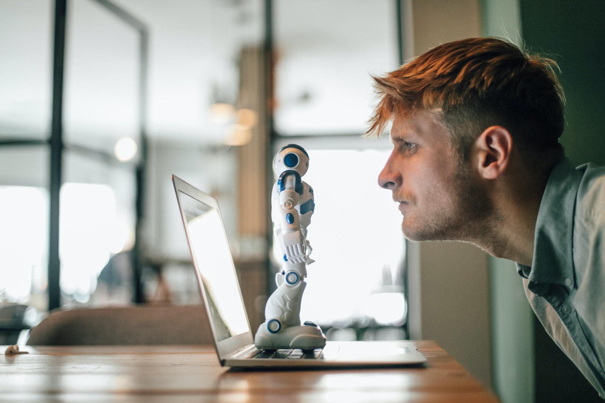 Man kijkt naar robot die op zijn laptop staat