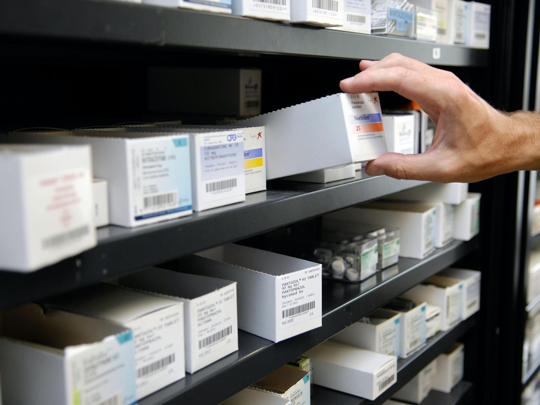Een hand die medicijnen uit een kast pakt
