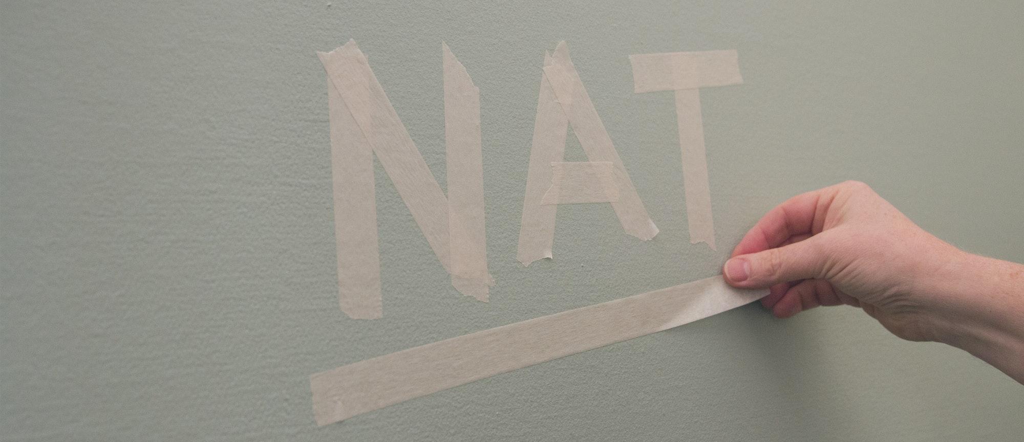 Een geschilderde wand met het woord 'nat' gemaakt van afplak-tape