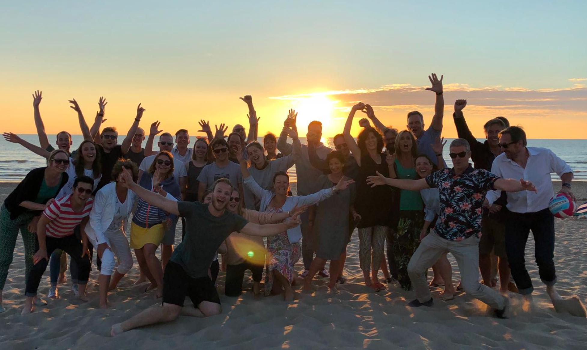 De zwaaiende medewerkers van Informaat op het strand
