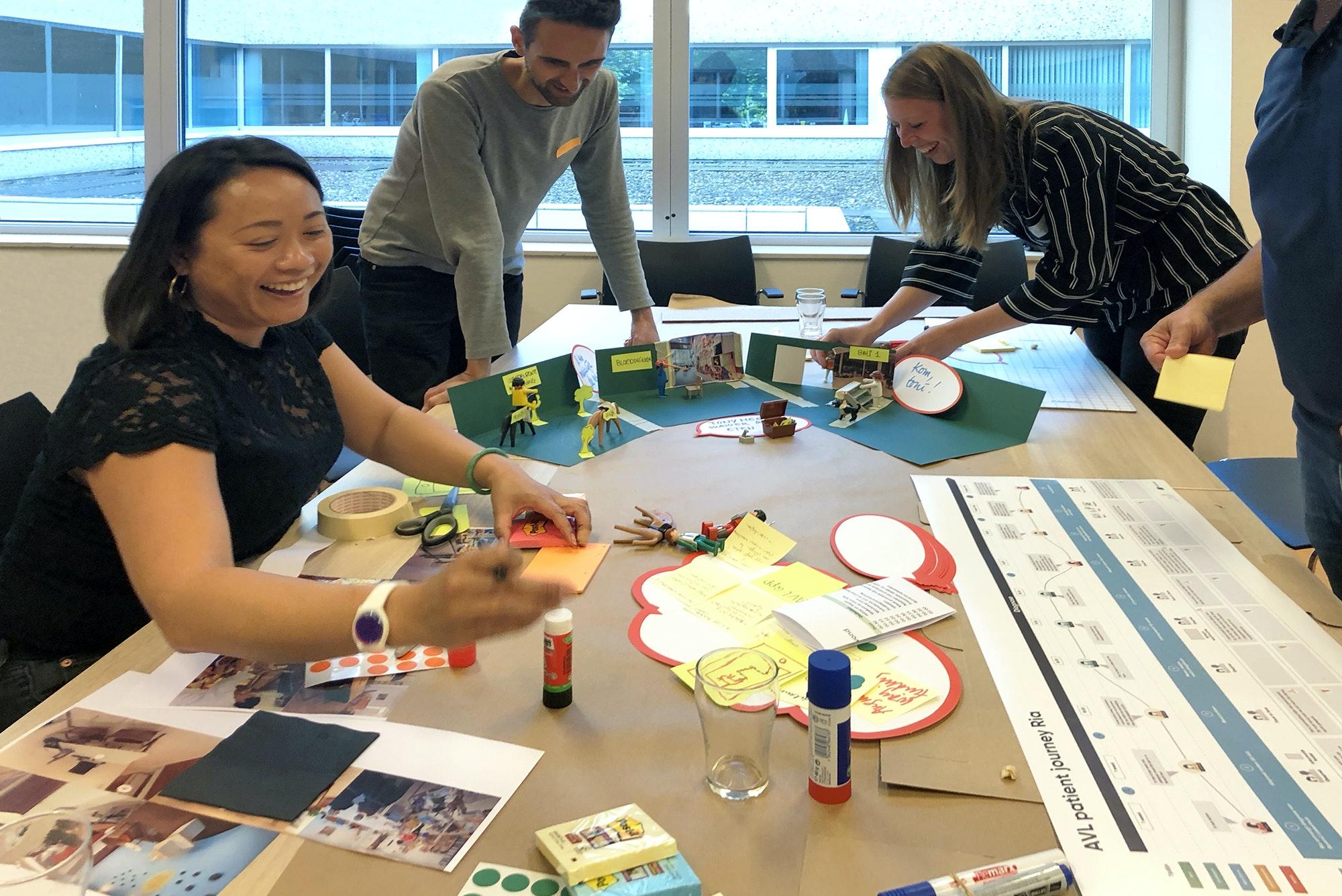 drie-mensen-aan-tafel-workshop-lachen