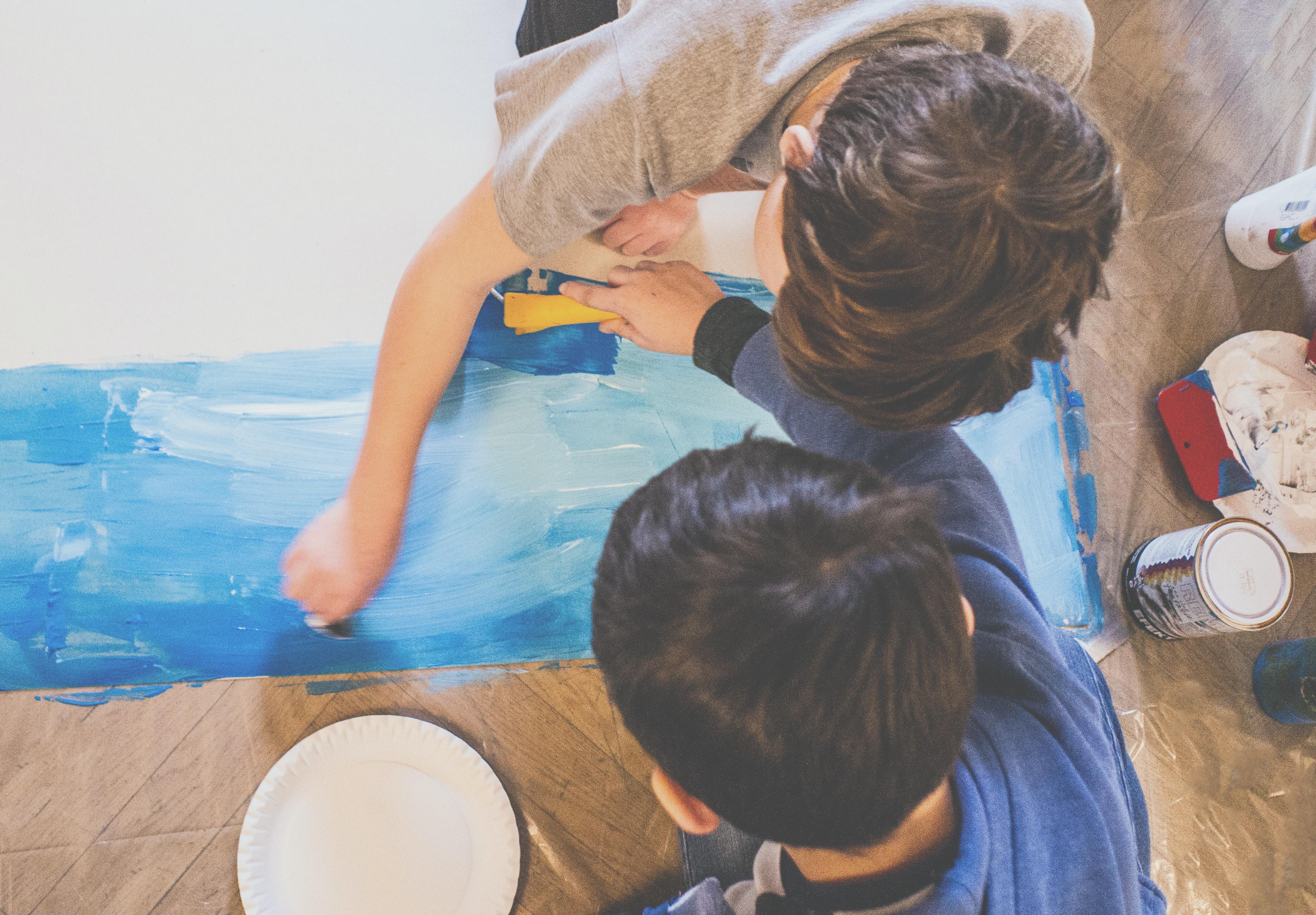 Dvě děti malují na papír na zemi modrou plochu v jednom z výtvarných kurzů ve Ville Pellé.