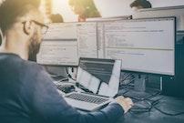 Developer programming in front of computer screens