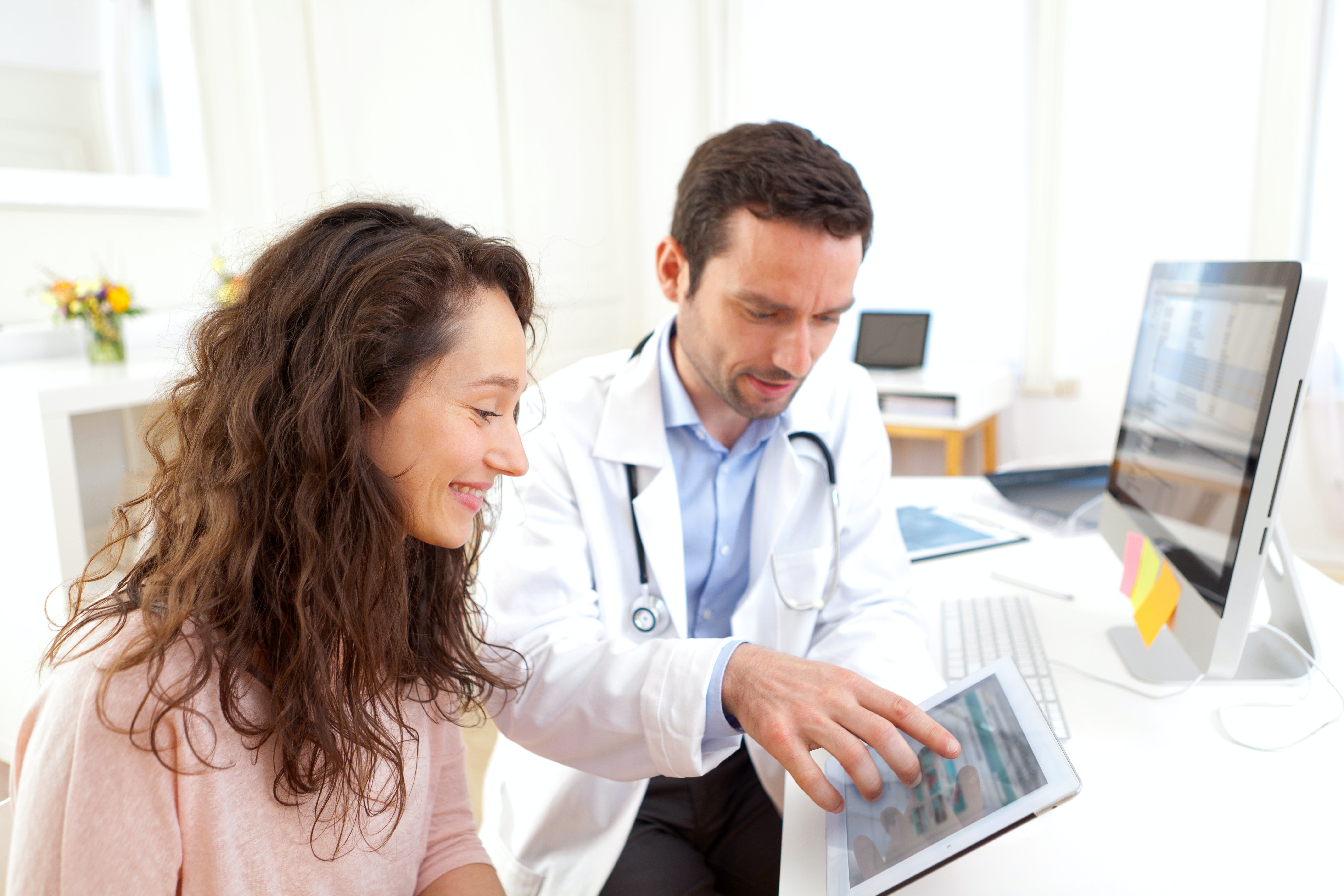 Doctor using computer and tablet to inform patient