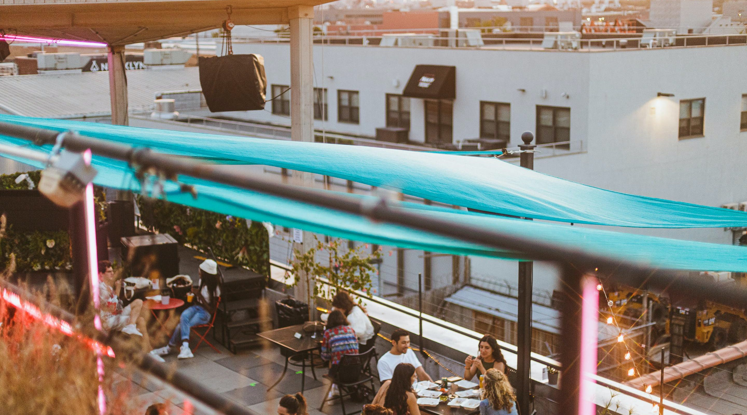 Several pairs and small groups of people sit, eat and drink at tables on the rooftop terrace