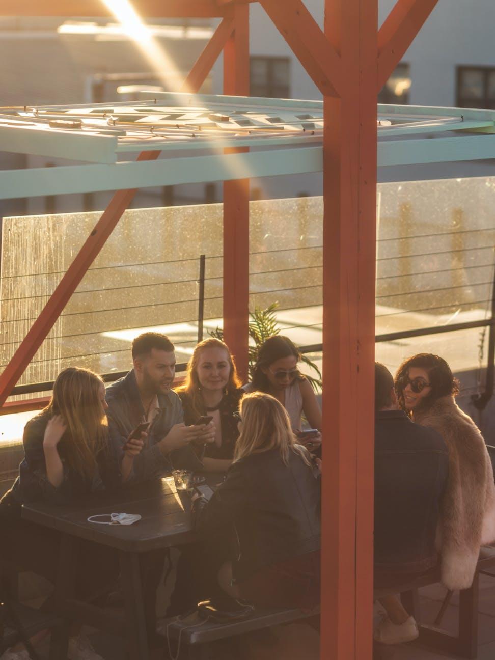 Group sitting at table at sundown