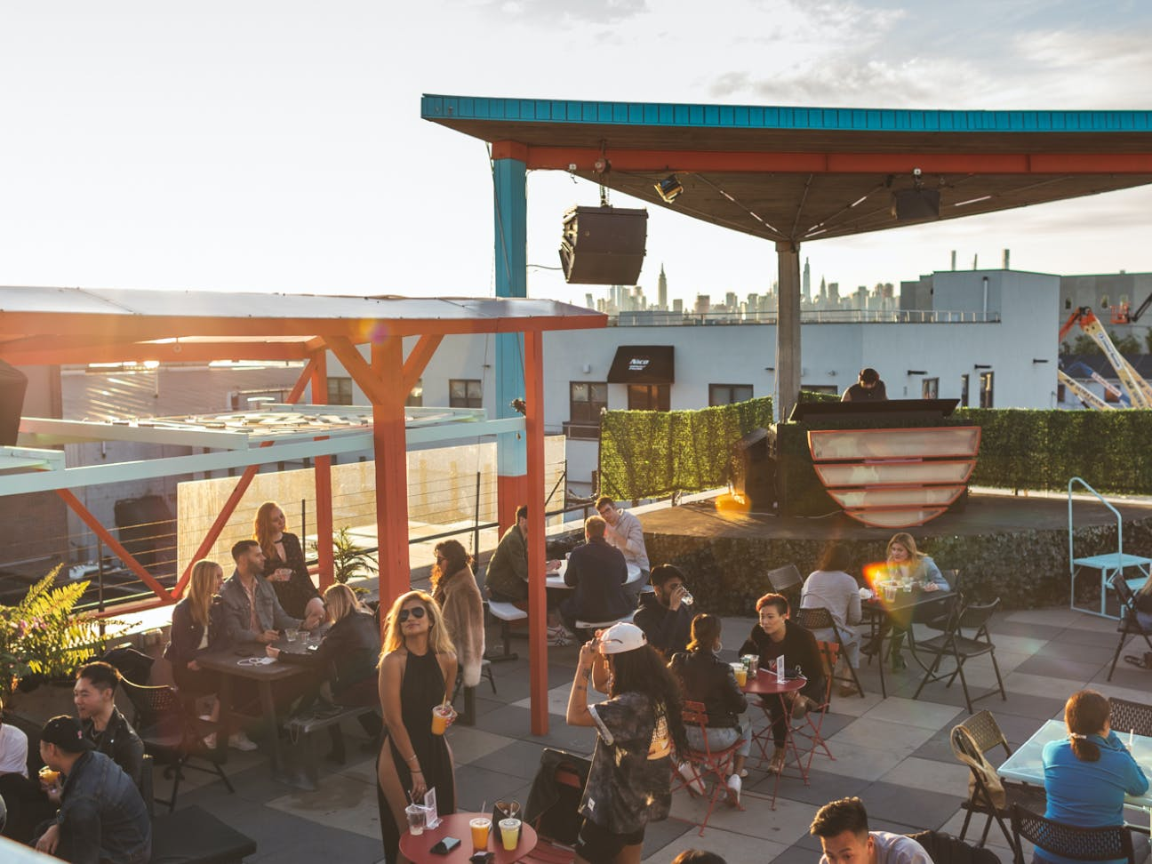 Groups sitting at tables on the rooftop with New York city skyline in the horizon