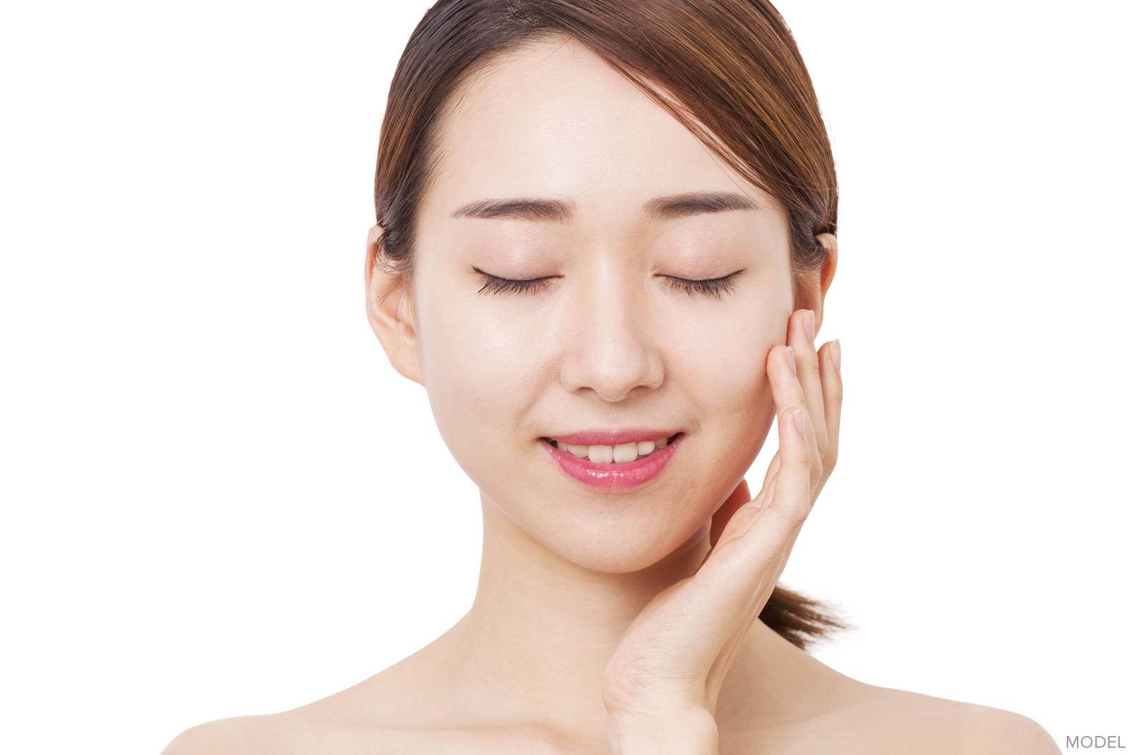 Woman closing eyes following eyelid surgery