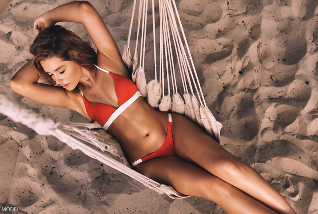 Woman lounging on beach in Hawaii after liposuction at Asia Pacific Plastic Surgery