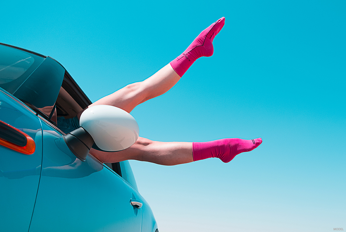 A woman happily puts her legs out of the car post thermiva treatment.