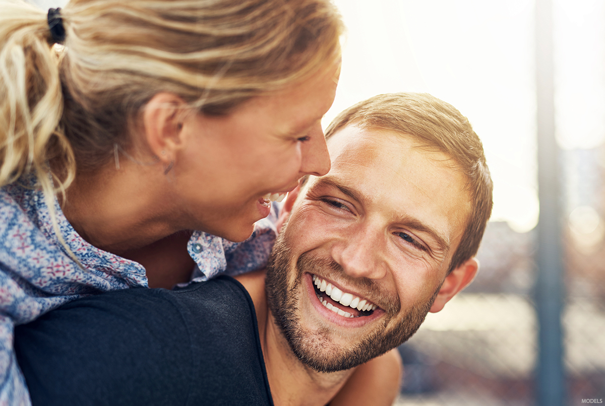 A man looks happy as he is complimented by his girlfriend about his hair.