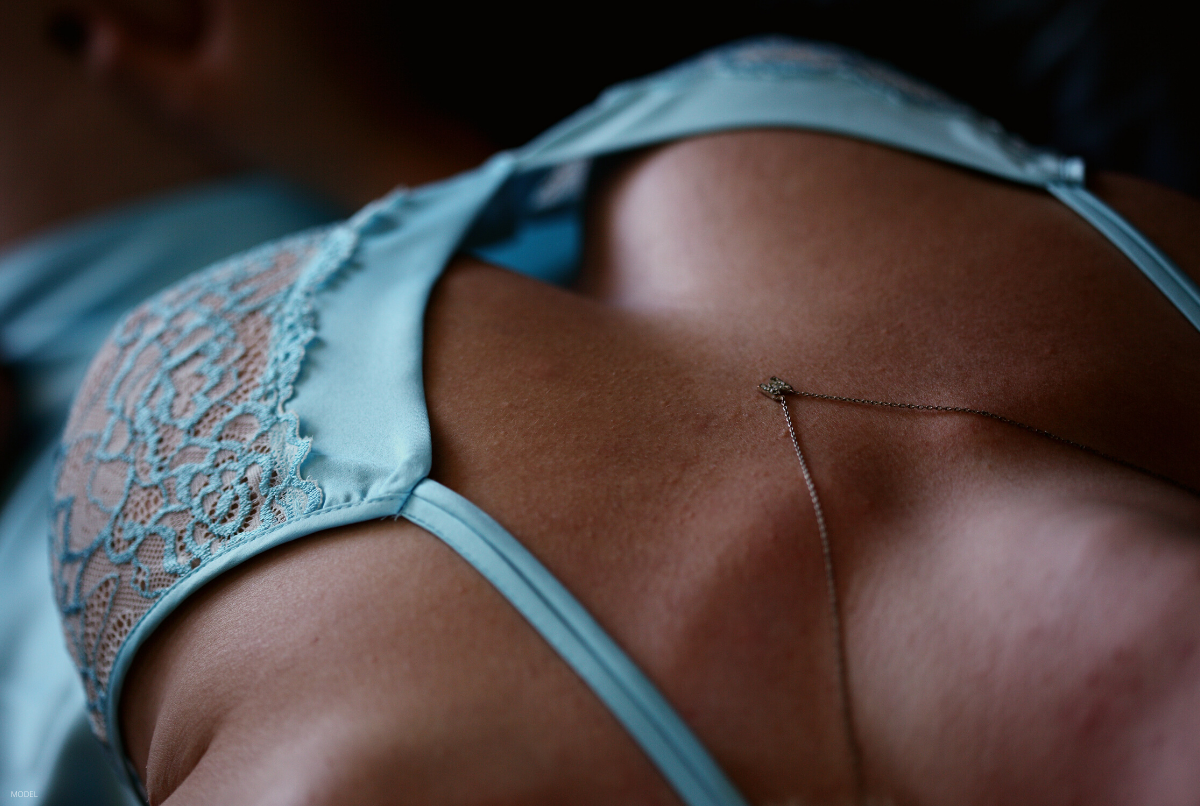A woman lays down after getting scar-less breast augmentation surgery.