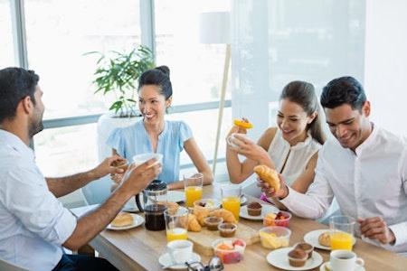 Büro Team frühstückt am Holztisch