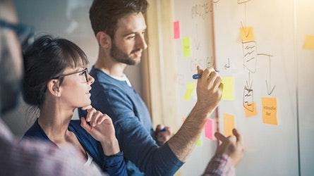 Kollegen stehen am White-Board und sammeln Ideen