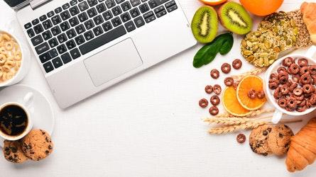 Frühstück im Büro mit Brötchen, Obst und Müsli