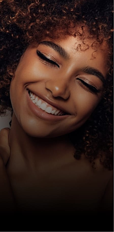 Beautiful woman with curly hair smiling with her eyes closed
