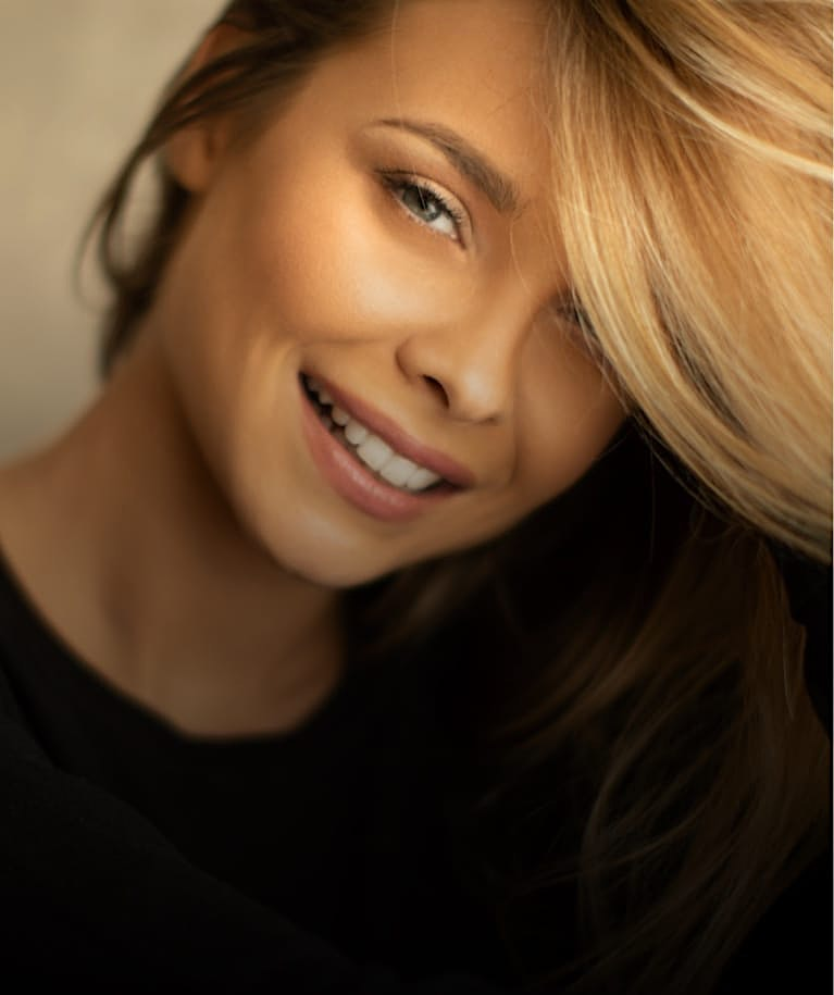 Blonde woman smiling with her hair over some of her face
