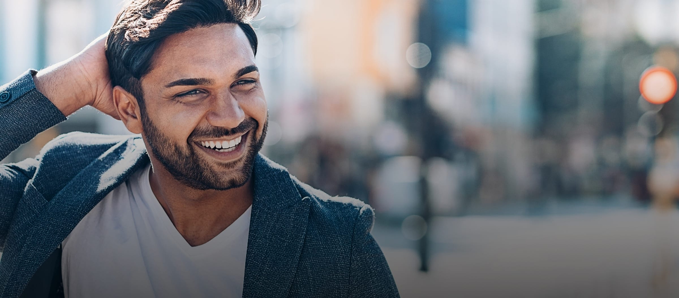 Man smiling outside, running his hand through his hair