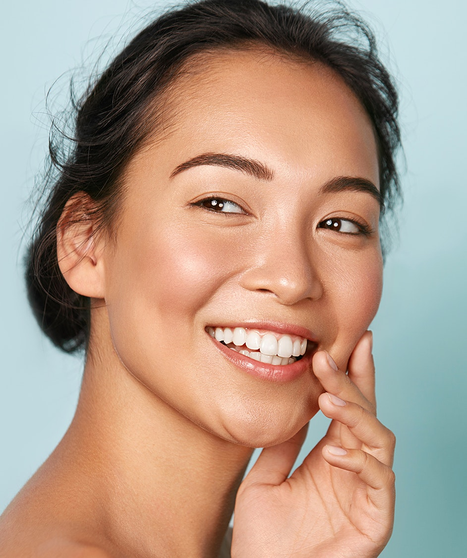 Beautiful woman with clear skin smiling, looking to the side
