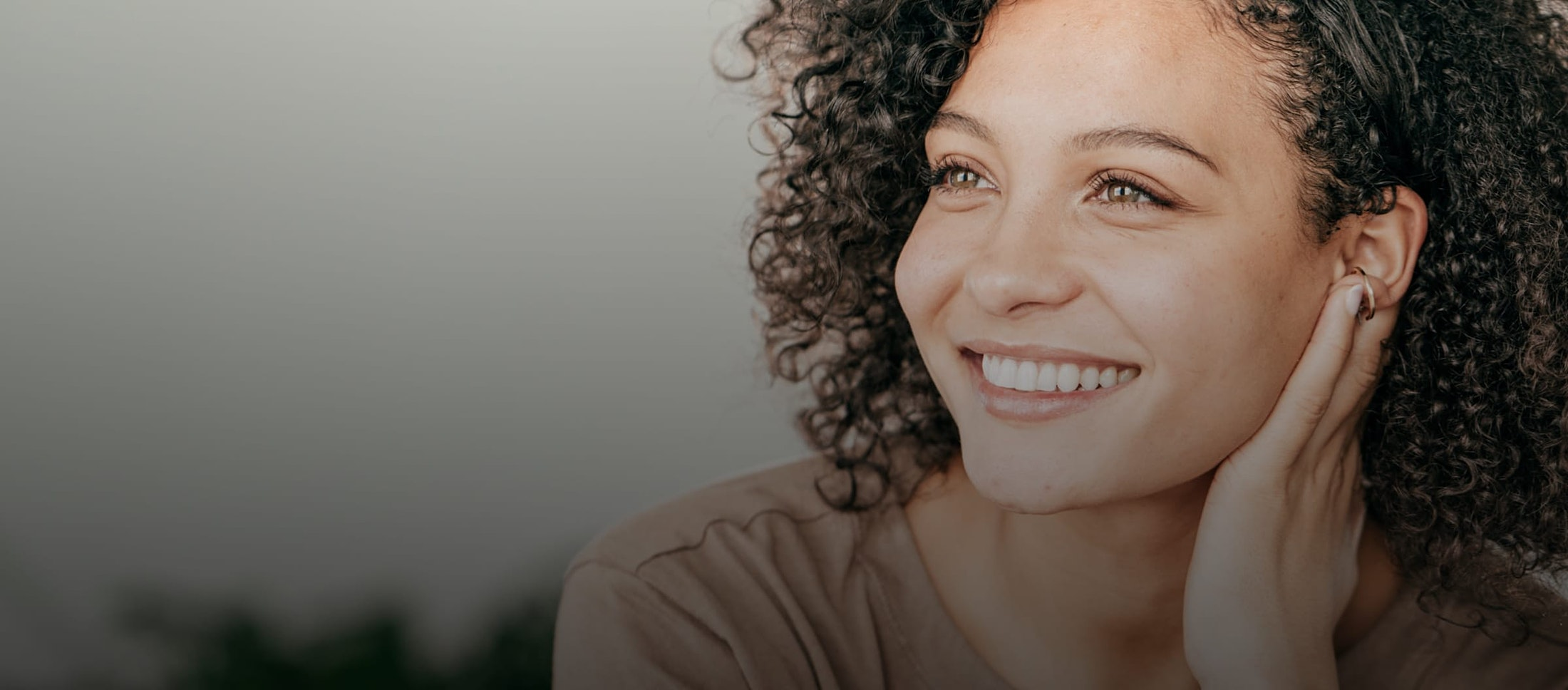 Woman with curly hair smiling, looking to the side