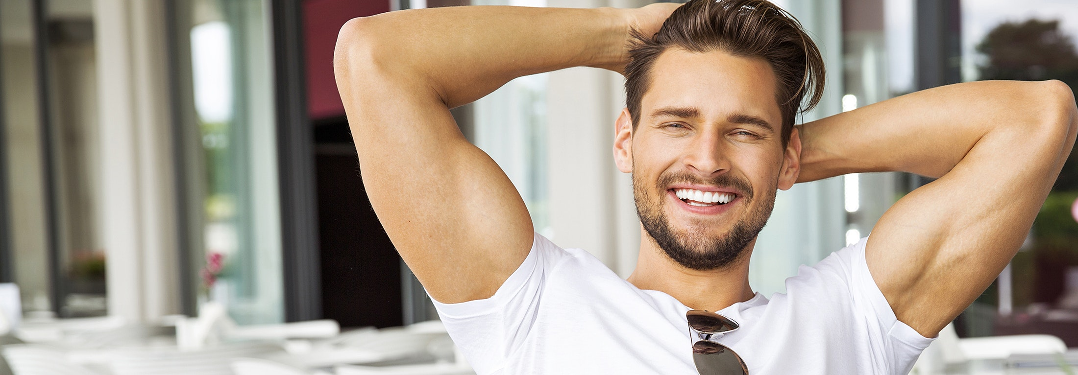 Handsome man smiling with his arms raised up behind his head