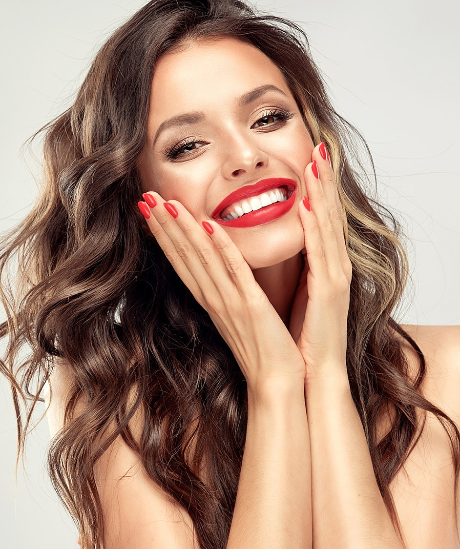 Beautiful woman with long curly hair smiling, wearing bright red lipstick