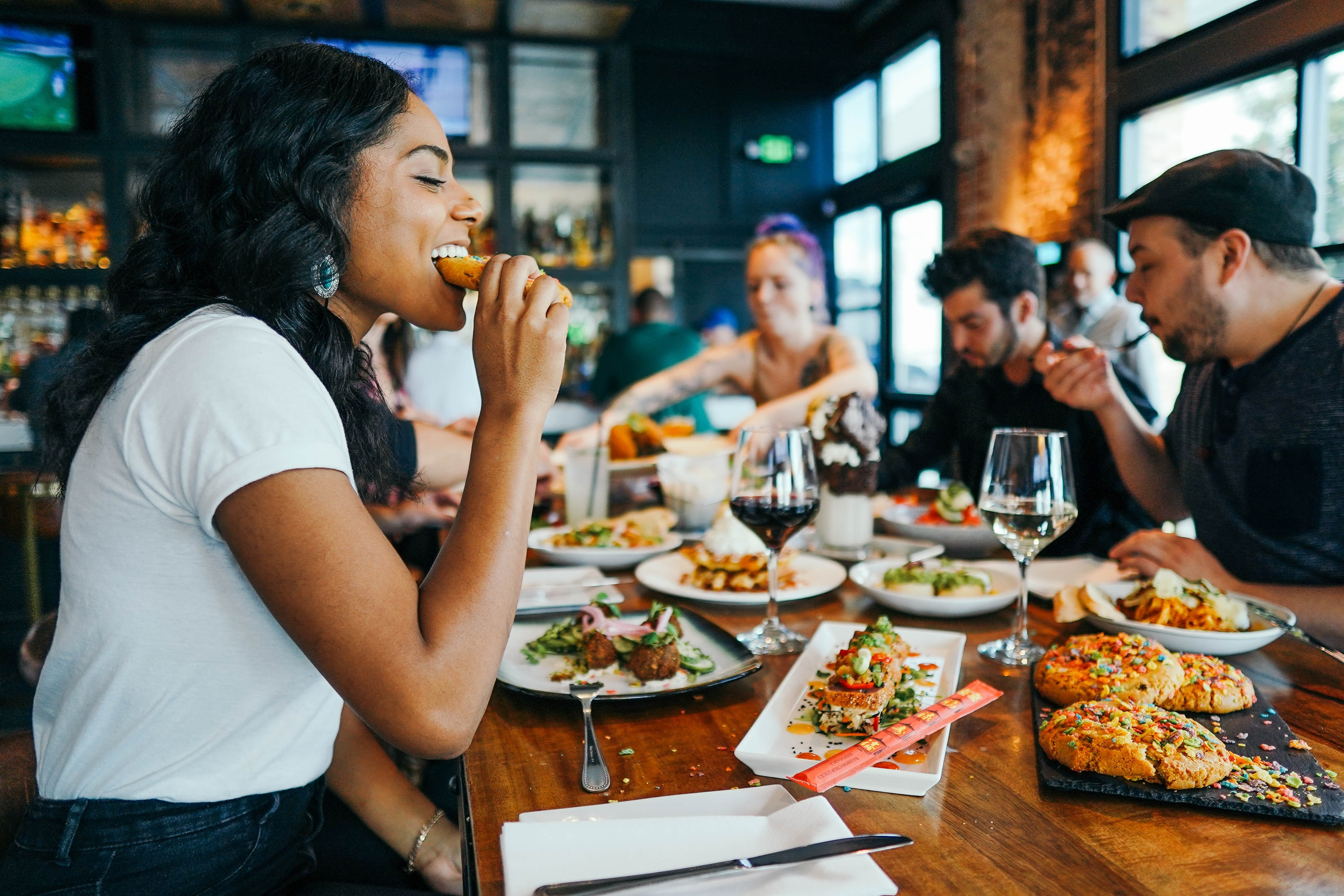 Woman eating healthy foods at restaurant with friends