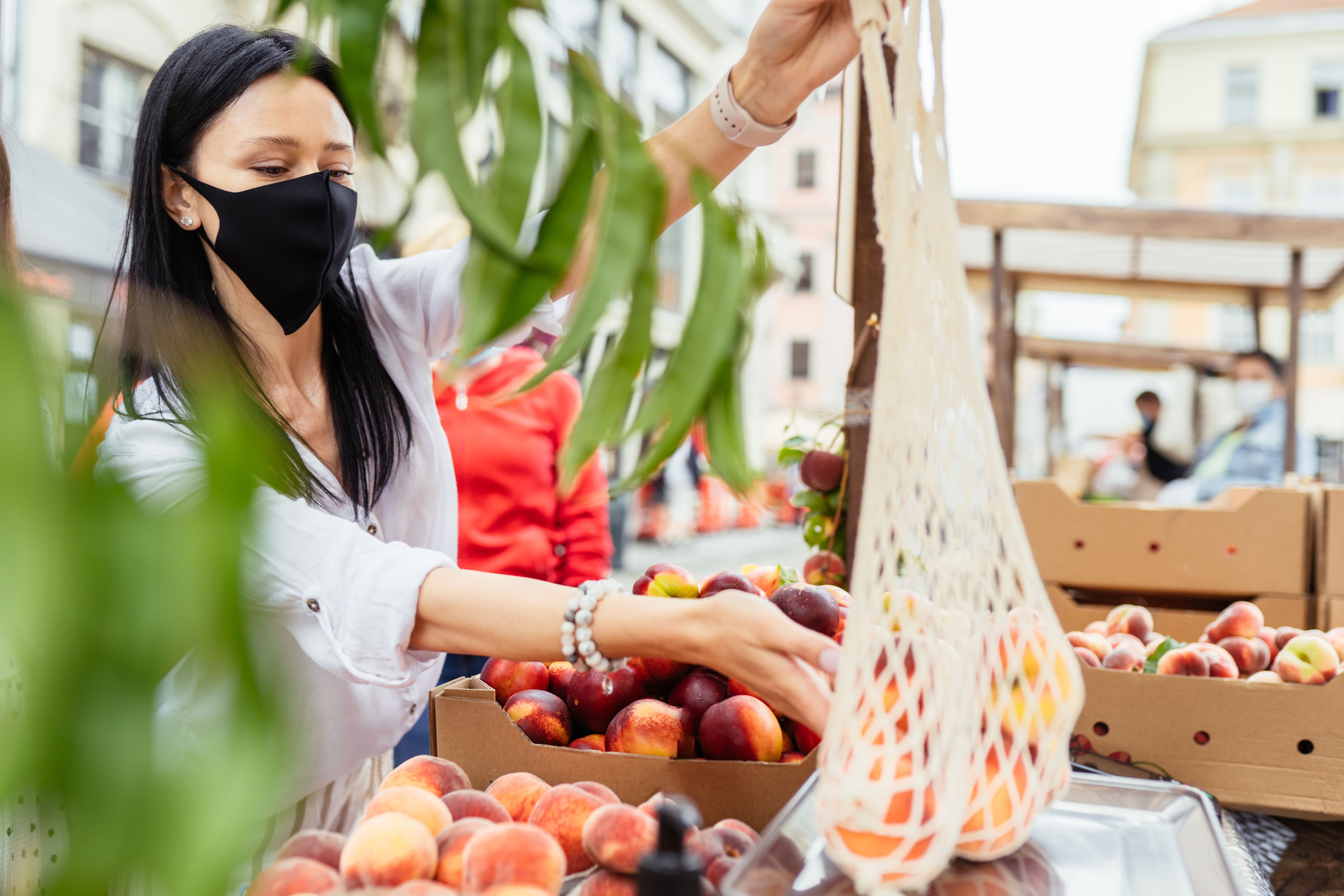 Woman in mask shopping for peaches at market