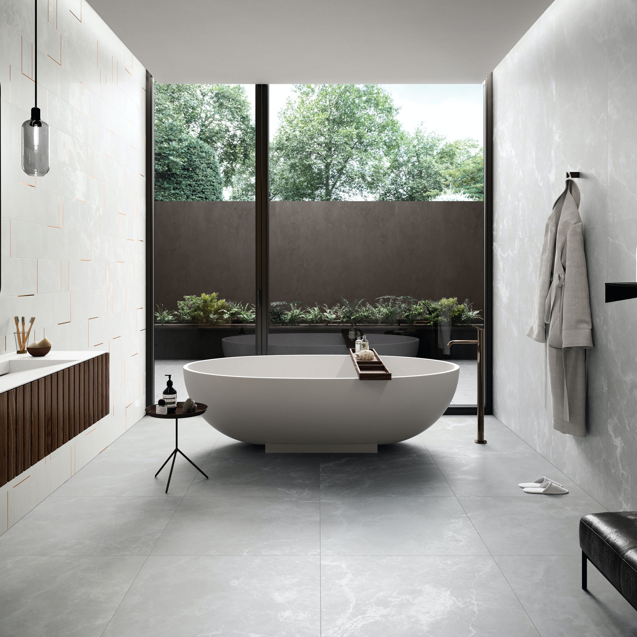 Sparkling light grey tiles on walls and floor in a large format. A bath sits in the centre of the room which looks out into a modern courtyard. On the left, we see a feature mosaic in the same tile with a bronze insert. A glimpse of a vanity and pendant can also be seen on the left. On the right a robe is hanging off the wall and we see a glimpse of a bench. The daylight shines off the floor tiles.