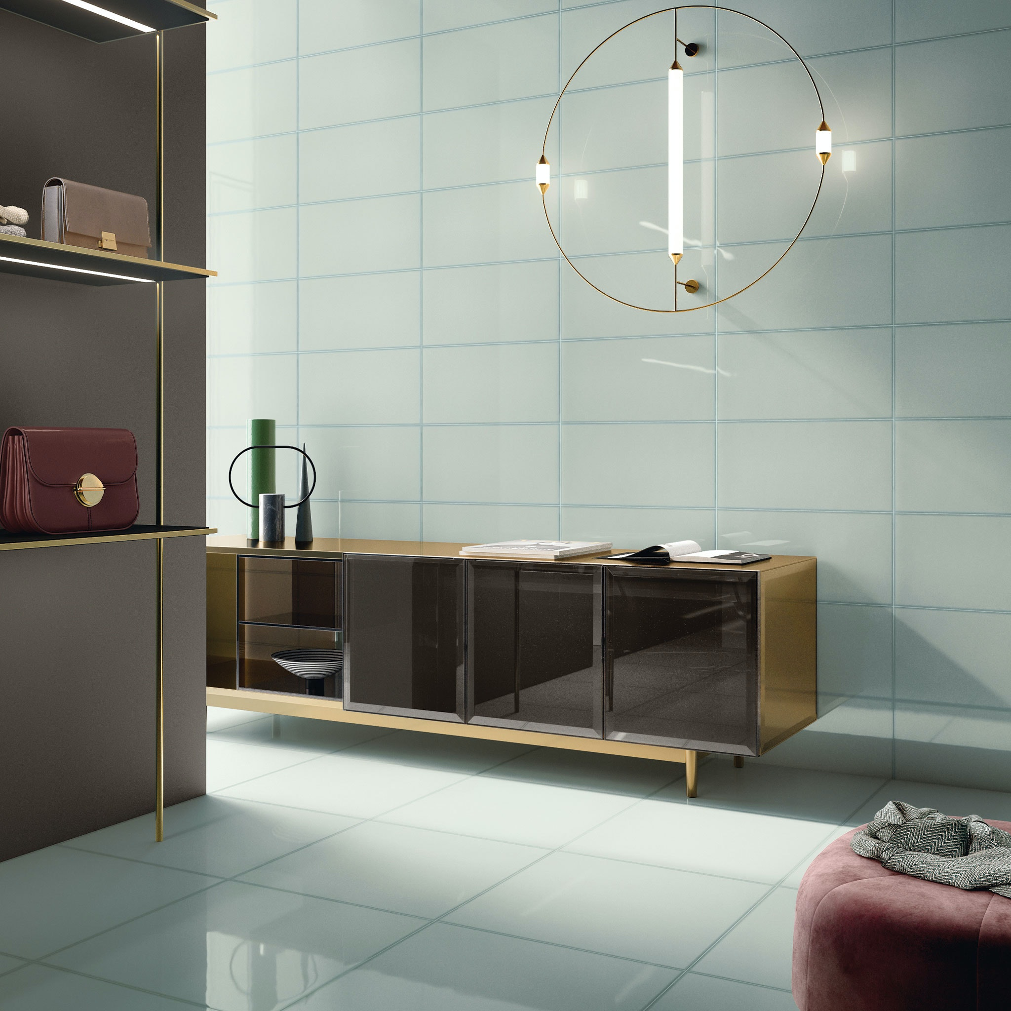 Glass-look light aqua coloured tiles on the floor and walls. Featuring a gold console table by the wall and a round modern pendant above it. Handbags are displayed on the left and a glimpse of a velvet ottoman can be seen on the bottom right.