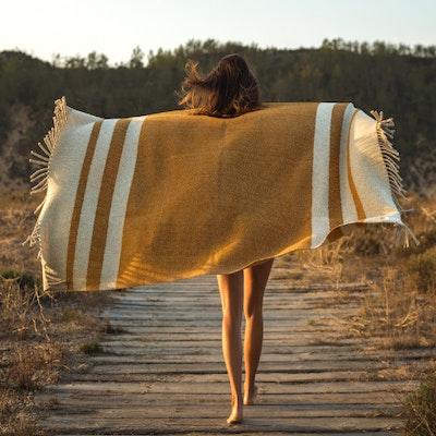 Donna che cammina in natura con coperta sulle spalle