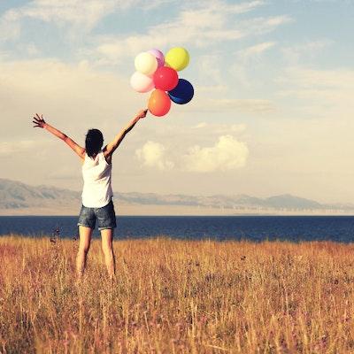 Donna in riva al mare con palloncini colorati