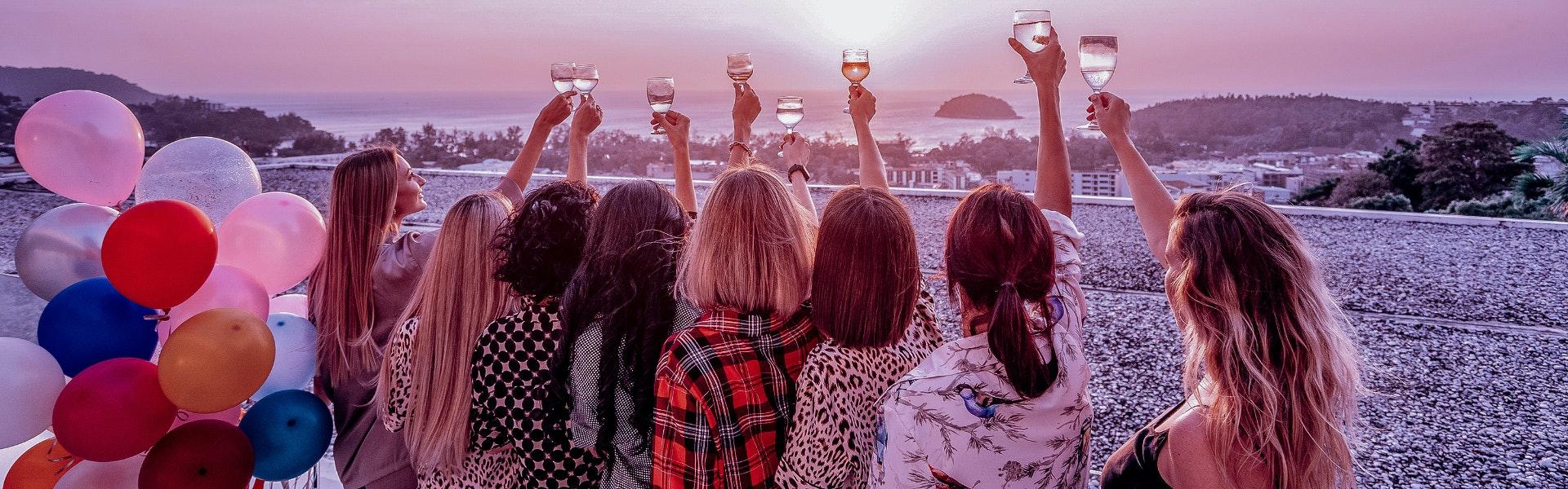 Donne in viaggio brindano al tramonto sul mare
