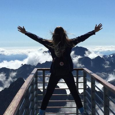 Donna in viaggio in montagna a braccia aperte al cielo