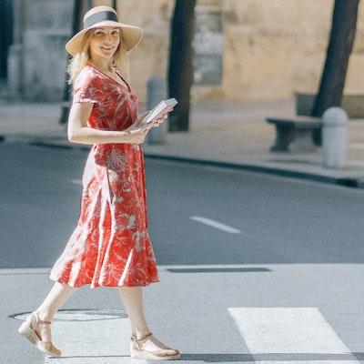 Donna in viaggio con vestito rosso e cappello di paglia