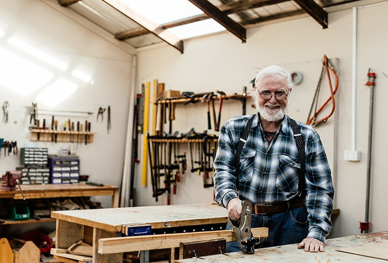 Man in his workshop surrounded by woodworking tools