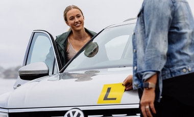 Learner driver and instructor standing by a car