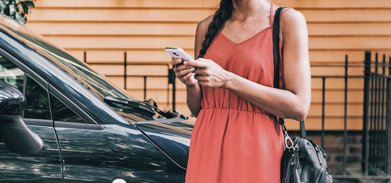 Young lady using her mobile phone next to her car