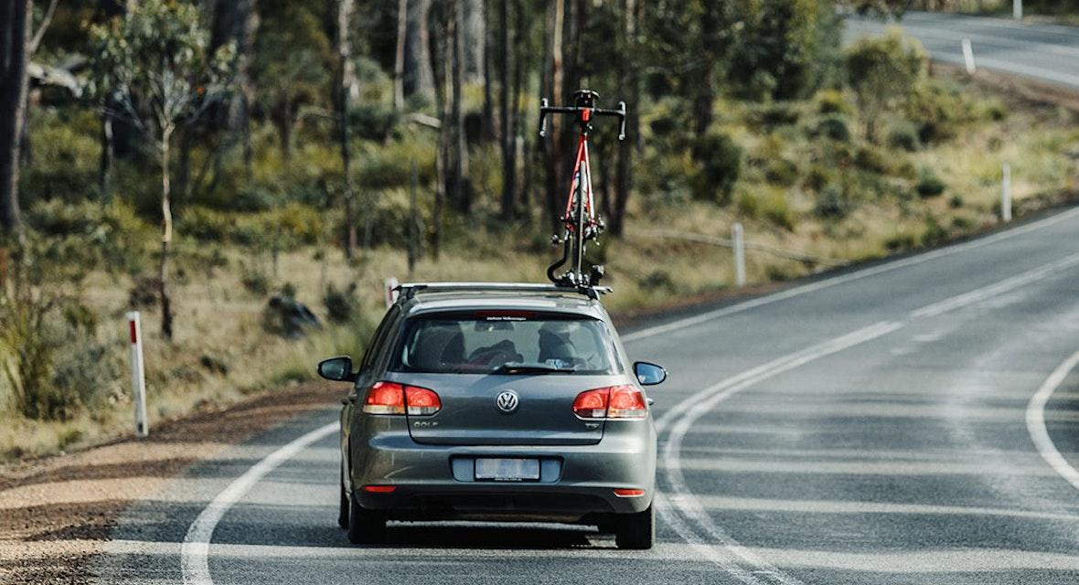 VW Hatchback with bike on roof racks driving on rural highway