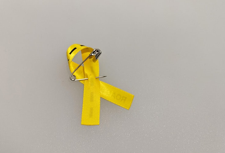 Yellow ribbon bow with a safety pin