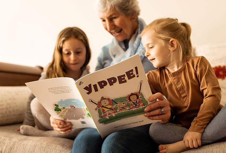 Grandmother with children reading Yippee book