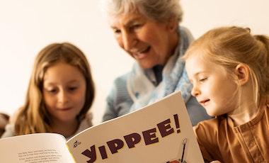 A grandmother reads to her grandchildren