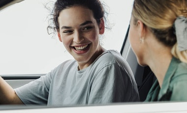 Girls chatting in the front of the car.