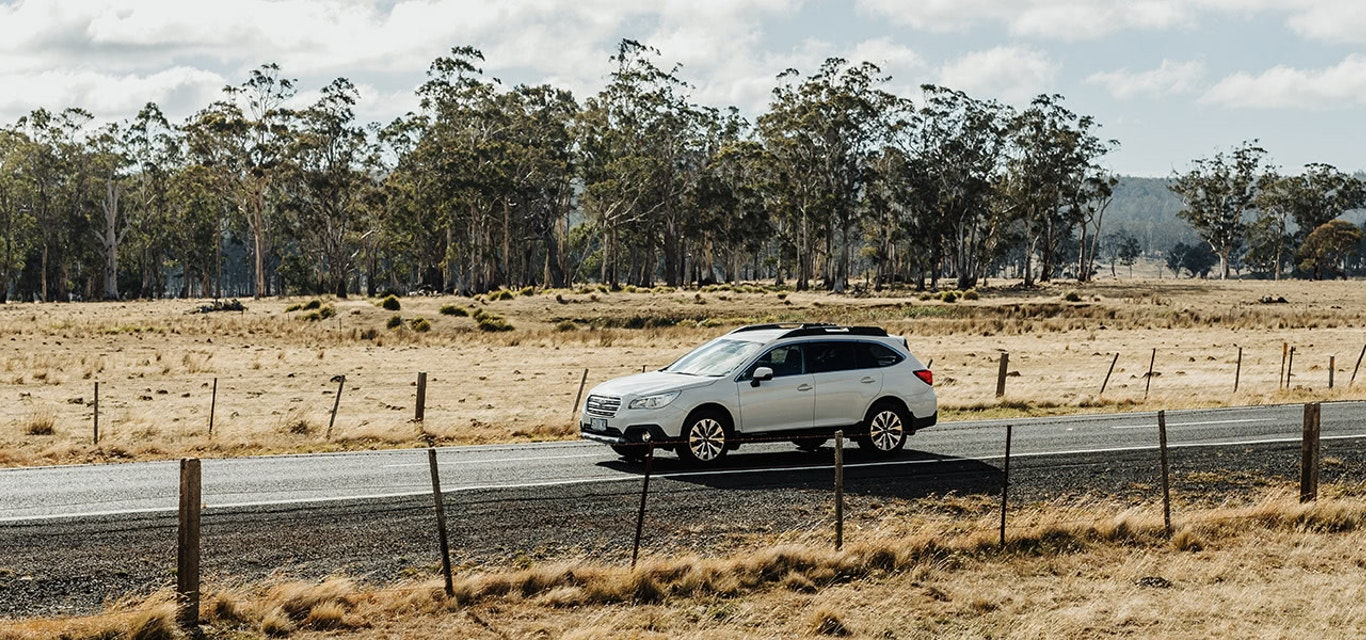 White Subaru Outback driving on country road
