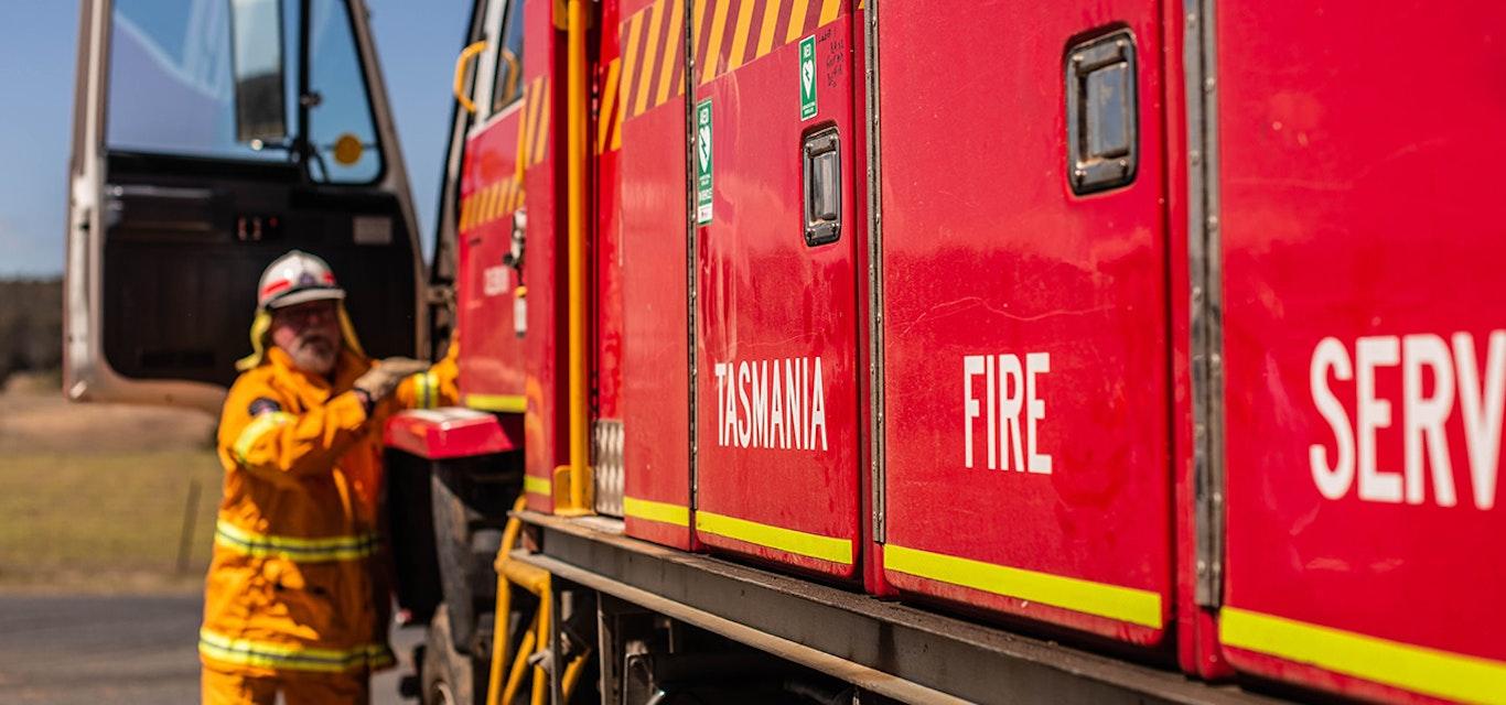 Fireman hopping into fire truck.