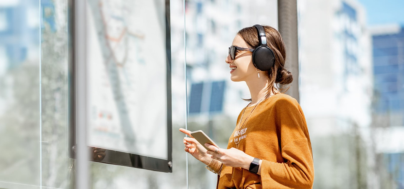 Woman wearing earphones and holding a mobile phone