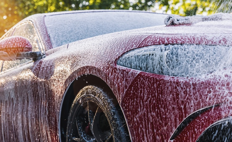 Red sedan being washed by hand