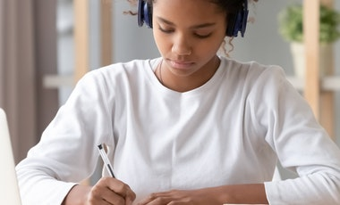 Student writing at a desk.