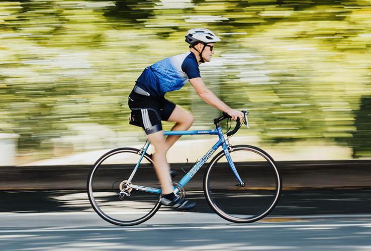 Man riding bike along road