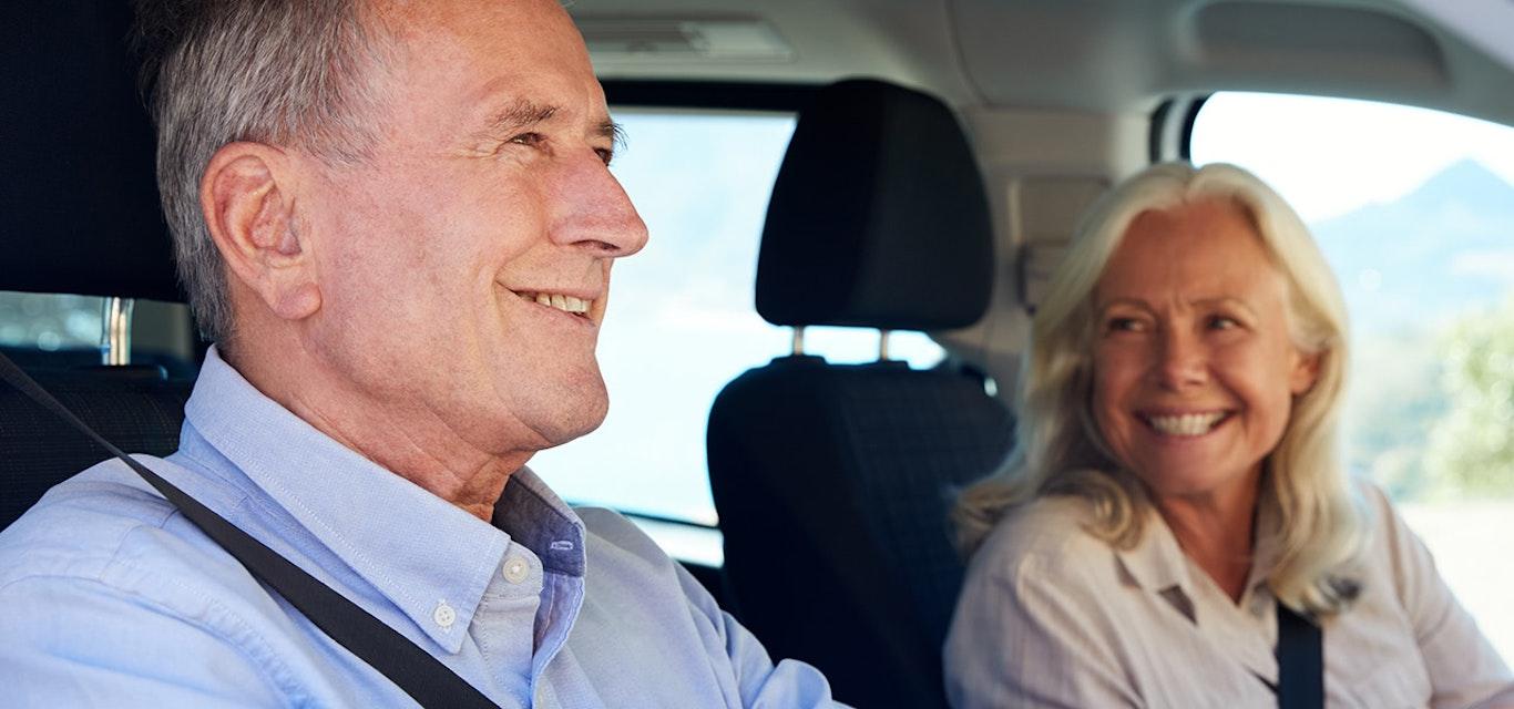 Man driving as woman smiles in passenger seat